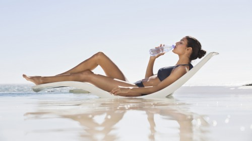 woman-at-beach-drinking-water