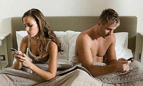 couple-au-lit-qui-regardent-leur-smarphone