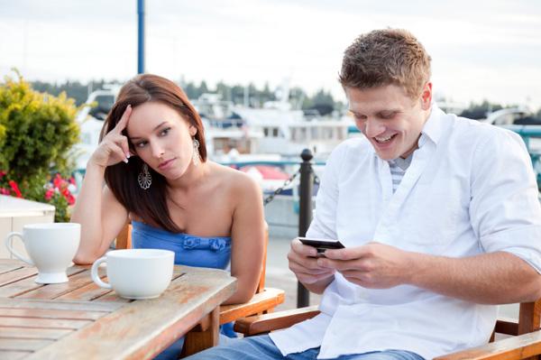 jeune-couple-homme-regarde-son-smartphone-femme-qui-fait-la-tête