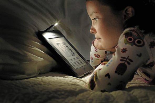 enfant-qui-lit-sur-une-liseuse-avec une lampe