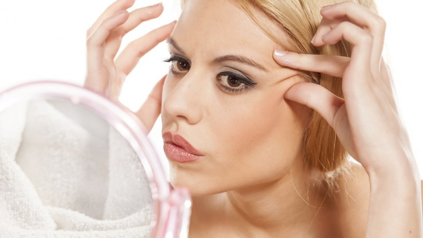 worried young woman checking her-wrinkles-around-her-eyes